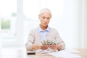 Senior woman counting money, frowning