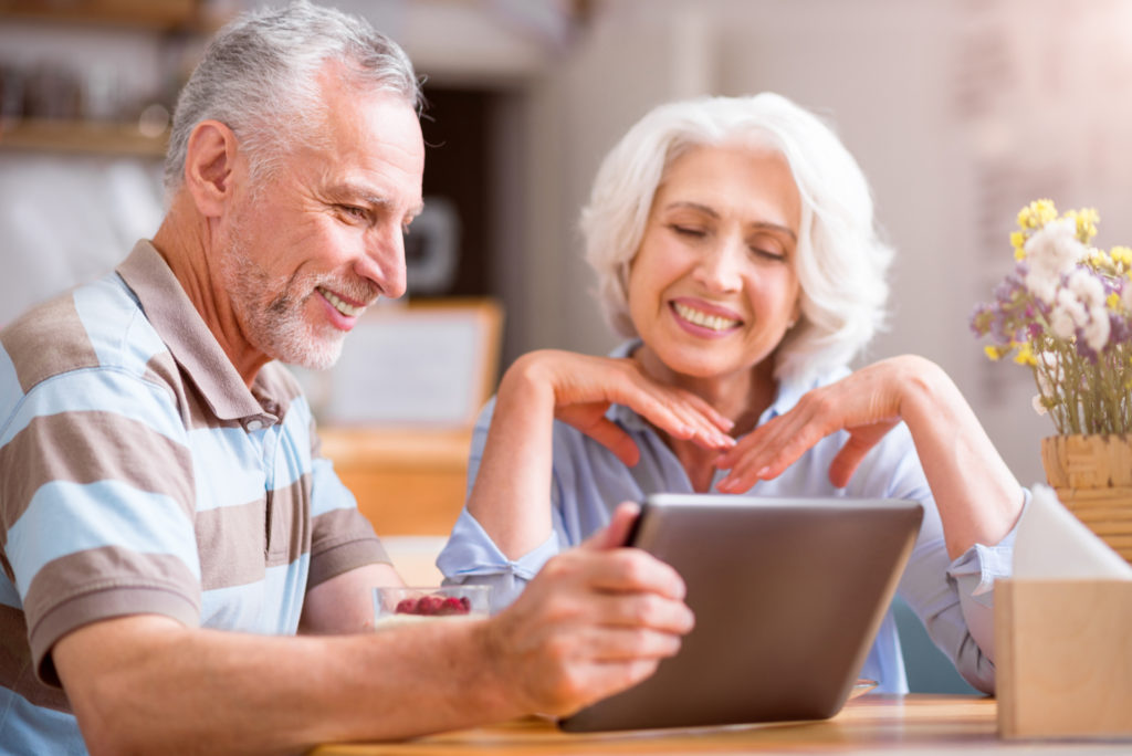 Boomer couple looking at tablet
