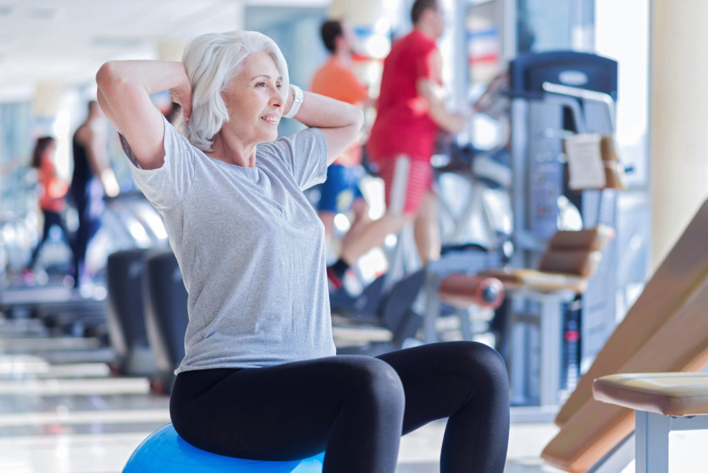 Middle aged woman exercising in gym