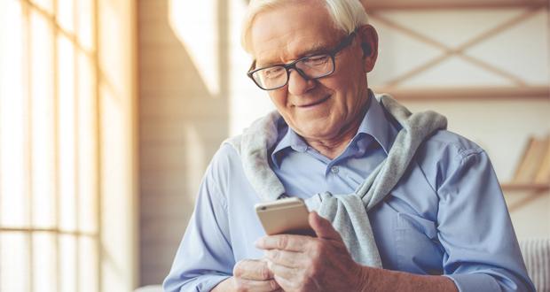 Older man on smartphone smiling
