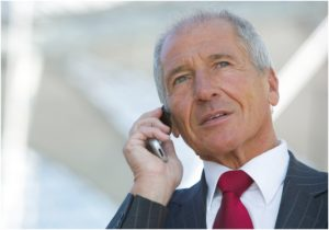Aelterer Manager telefoniert mit Handy, Portraet