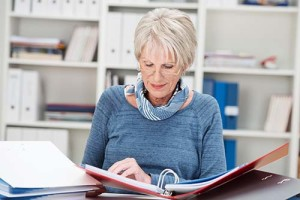 Elderly businesswoman hard at work at the office sitting at her desk reading from a business binder