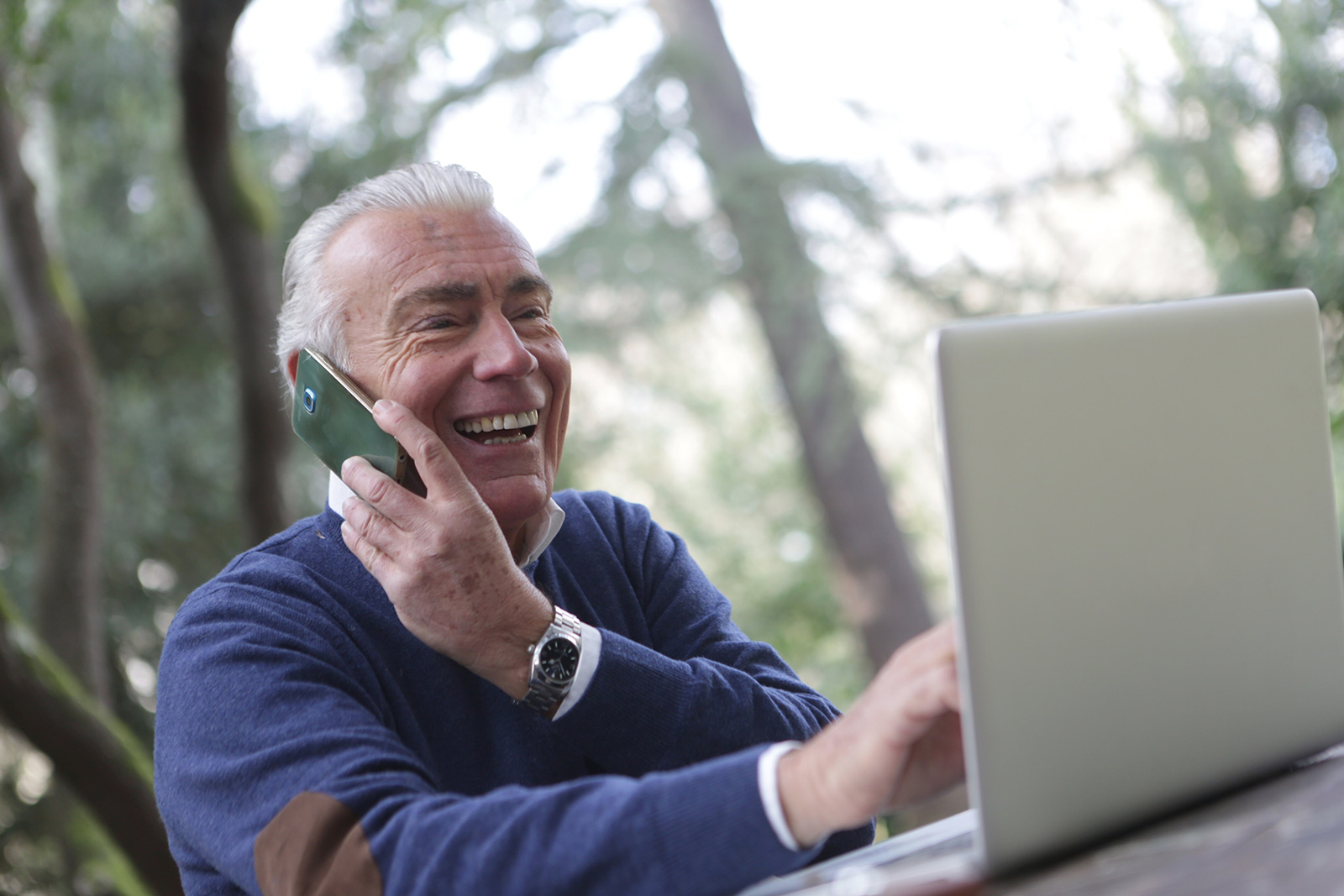 senior man on phone in front of computer